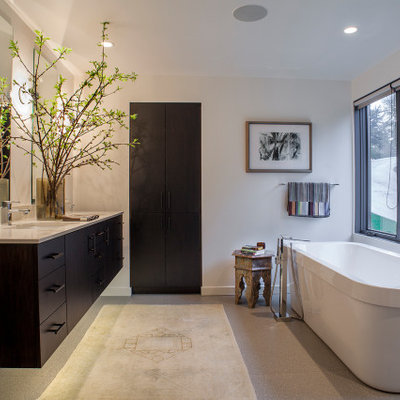 Freestanding bathtub - large contemporary master gray floor freestanding bathtub idea in Portland with flat-panel cabinets, dark wood cabinets, white walls, an undermount sink and beige countertops