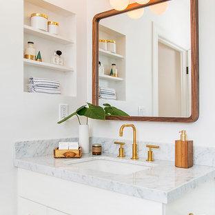Diseño de cuarto de baño retro, de tamaño medio, con armarios con paneles lisos, puertas de armario blancas, paredes blancas, lavabo bajoencimera, encimera de mármol y encimeras grises