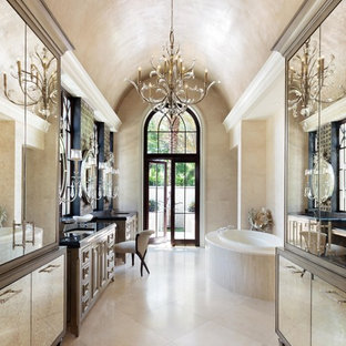 Inspiration for a mediterranean master beige tile beige floor drop-in bathtub remodel in Miami with furniture-like cabinets, beige cabinets, beige walls and an undermount sink