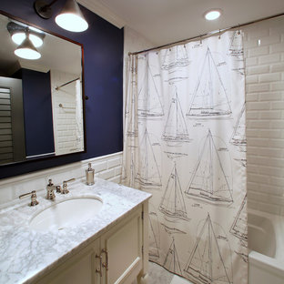 Alcove bathtub - tropical white tile and subway tile alcove bathtub idea in Tampa with an undermount sink, white cabinets, recessed-panel cabinets and gray countertops