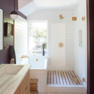 サンフランシスコのミッドセンチュリースタイルのおしゃれなマスターバスルーム (開き戸のシャワー、フラットパネル扉のキャビネット、淡色木目調キャビネット、ドロップイン型浴槽、コーナー設置型シャワー、白いタイル、サブウェイタイル、紫の壁、大理石の床、アンダーカウンター洗面器、白い床、白い洗面カウンター) の写真