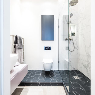 Photo of a medium sized contemporary bathroom in London with flat-panel cabinets, white cabinets, an alcove bath, a wall mounted toilet, white tiles, marble tiles, white walls, a vessel sink, multi-coloured floors and an open shower.