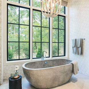 Maritim inredning av ett en-suite badrum, med ett fristående badkar, vita väggar och vitt golv