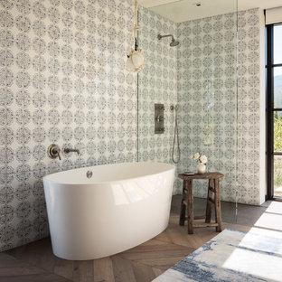Idee per una stanza da bagno country con vasca freestanding, doccia a filo pavimento, piastrelle multicolore, pavimento in legno massello medio, pavimento marrone e doccia aperta