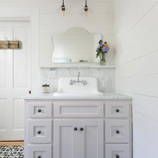 Diseño de cuarto de baño de estilo americano, de tamaño medio, con armarios estilo shaker, puertas de armario blancas, ducha esquinera, sanitario de una pieza, baldosas y/o azulejos blancas y negros, paredes blancas y lavabo bajoencimera