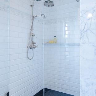 Diseño de cuarto de baño principal, tradicional, de tamaño medio, con armarios estilo shaker, ducha esquinera, baldosas y/o azulejos blancos, baldosas y/o azulejos de cerámica, paredes azules, suelo de baldosas de cerámica, suelo negro y ducha con puerta con bisagras