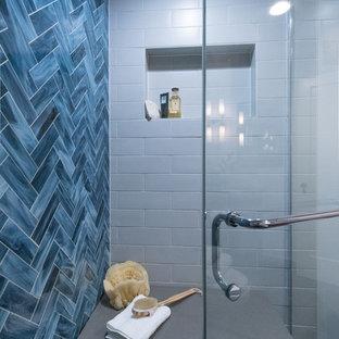 Foto de cuarto de baño con ducha, bohemio, pequeño, con armarios estilo shaker, puertas de armario de madera en tonos medios, ducha empotrada, sanitario de una pieza, baldosas y/o azulejos grises, baldosas y/o azulejos de vidrio, paredes azules, suelo de baldosas de porcelana, lavabo bajoencimera y encimera de cuarzo compacto