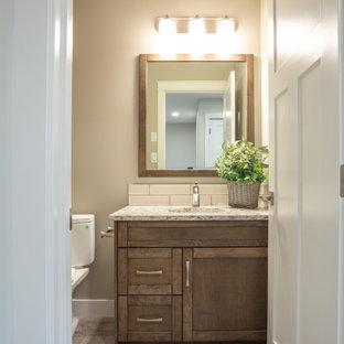 Kleines Rustikales Badezimmer mit Schrankfronten mit vertiefter Füllung, braunen Schränken, Badewanne in Nische, Duschbadewanne, Toilette mit Aufsatzspülkasten, weißen Fliesen, Metrofliesen, beiger Wandfarbe, Vinylboden, Unterbauwaschbecken, Granit-Waschbecken/Waschtisch, grauem Boden, Duschvorhang-Duschabtrennung und weißer Waschtischplatte in Sonstige