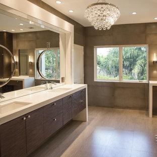 ヒューストンの巨大なコンテンポラリースタイルのおしゃれなマスターバスルーム (アンダーカウンター洗面器、家具調キャビネット、濃色木目調キャビネット、珪岩の洗面台、置き型浴槽、シャワー付き浴槽、壁掛け式トイレ、グレーのタイル、磁器タイル、マルチカラーの壁、磁器タイルの床) の写真