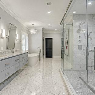 Immagine di una stanza da bagno con doccia tradizionale di medie dimensioni con ante lisce, ante blu, vasca freestanding, doccia ad angolo, WC monopezzo, piastrelle grigie, piastrelle di marmo, pareti bianche, pavimento in marmo, lavabo da incasso, top in quarzite, pavimento grigio e top bianco
