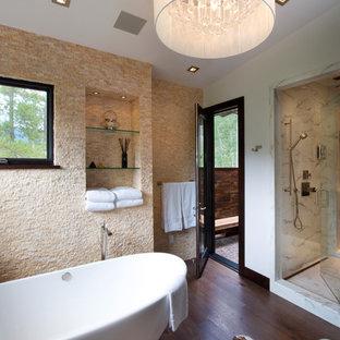 Diseño de cuarto de baño principal, rústico, grande, con bañera exenta, ducha empotrada, baldosas y/o azulejos beige, baldosas y/o azulejos de piedra, paredes blancas, suelo de madera oscura, armarios con paneles lisos, puertas de armario de madera en tonos medios y encimera de granito