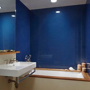 Modelo de cuarto de baño principal, actual, de tamaño medio, con lavabo suspendido, bañera encastrada sin remate, baldosas y/o azulejos azules, baldosas y/o azulejos de vidrio laminado, suelo de madera en tonos medios, paredes azules, armarios abiertos y suelo marrón