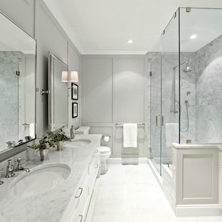 Inspiration for a large traditional ensuite bathroom in New York with shaker cabinets, white cabinets, white tiles, stone tiles, grey walls, marble worktops, a corner shower and a hinged door.