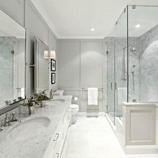 ニューヨークの広いトランジショナルスタイルのおしゃれなマスターバスルーム (シェーカースタイル扉のキャビネット、白いキャビネット、白いタイル、石タイル、グレーの壁、大理石の洗面台、コーナー設置型シャワー、開き戸のシャワー) の写真