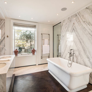 Photo of an ensuite bathroom in London with open cabinets, a freestanding bath, a submerged sink and white worktops.