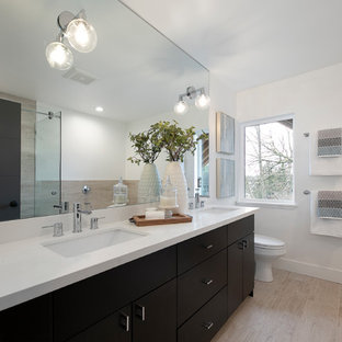 Inspiration for a transitional 3/4 beige tile beige floor corner shower remodel in Los Angeles with flat-panel cabinets, black cabinets, white walls, an undermount sink and white countertops