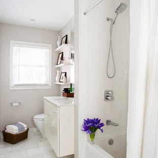 Small trendy white tile and subway tile marble floor and white floor bathroom photo in Atlanta with white cabinets, an undermount sink, marble countertops, a one-piece toilet, gray walls and flat-panel cabinets