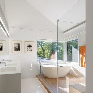 サンフランシスコの大きいコンテンポラリースタイルのおしゃれなマスターバスルーム (一体型シンク、白いキャビネット、置き型浴槽、コーナー設置型シャワー、白い壁、フラットパネル扉のキャビネット、白いタイル、白い床、開き戸のシャワー) の写真