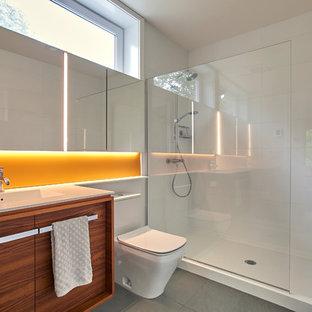 Imagen de cuarto de baño con ducha, minimalista, de tamaño medio, con armarios con paneles lisos, puertas de armario de madera oscura, ducha empotrada, urinario, baldosas y/o azulejos blancos, baldosas y/o azulejos de vidrio, paredes blancas, suelo de baldosas de porcelana, lavabo integrado, encimera de acrílico, suelo gris, ducha abierta y encimeras blancas
