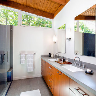 This is an example of a mid-sized midcentury master bathroom in Los Angeles with flat-panel cabinets, medium wood cabinets, an alcove shower, a one-piece toilet, blue tile, ceramic tile, white walls, ceramic floors, an undermount sink, engineered quartz benchtops, grey floor, a hinged shower door and grey benchtops.