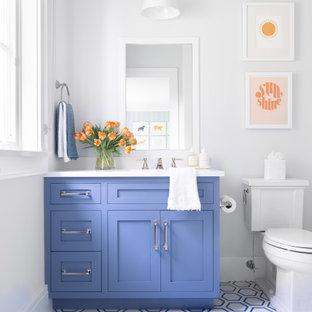 Mittelgroßes Klassisches Kinderbad mit Schrankfronten mit vertiefter Füllung, blauen Schränken, Eckbadewanne, Duschbadewanne, Toilette mit Aufsatzspülkasten, weißen Fliesen, Keramikfliesen, weißer Wandfarbe, Zementfliesen, integriertem Waschbecken, Marmor-Waschbecken/Waschtisch, blauem Boden, Duschvorhang-Duschabtrennung und weißer Waschtischplatte in New York