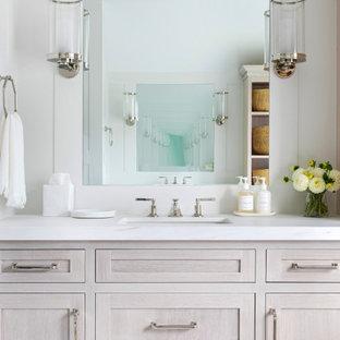 Bild på ett mycket stort vintage vit vitt en-suite badrum, med luckor med infälld panel, skåp i ljust trä, ett badkar med tassar, en dusch i en alkov, en toalettstol med hel cisternkåpa, vit kakel, vita väggar, ett integrerad handfat, marmorbänkskiva, vitt golv och dusch med gångjärnsdörr