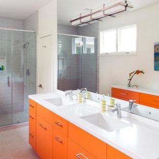 Immagine di una stanza da bagno per bambini minimalista con ante lisce, ante arancioni, doccia alcova, WC a due pezzi, piastrelle grigie, piastrelle di vetro, pareti bianche, pavimento in gres porcellanato, lavabo sottopiano e top in quarzo composito