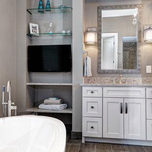 Пример оригинального дизайна: главная ванная комната в стиле современная классика с врезной раковиной, белыми фасадами, столешницей из искусственного кварца, отдельно стоящей ванной, серой плиткой, плиткой под дерево, серыми стенами и полом из керамической плитки