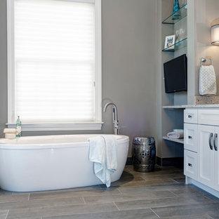 Foto di una stanza da bagno padronale tradizionale con lavabo sottopiano, ante bianche, top in quarzo composito, vasca freestanding, WC monopezzo, piastrelle grigie, piastrelle effetto legno, pareti grigie e pavimento con piastrelle in ceramica