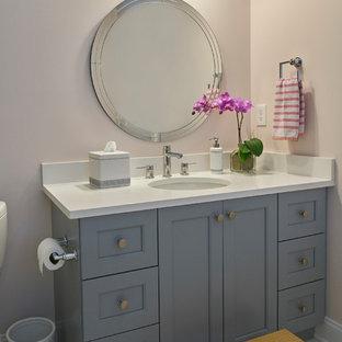 Diseño de cuarto de baño con ducha, tradicional renovado, de tamaño medio, con armarios con paneles empotrados, puertas de armario grises, bañera empotrada, combinación de ducha y bañera, paredes rosas, suelo de mármol, lavabo bajoencimera, encimera de cuarzo compacto, suelo gris y encimeras blancas