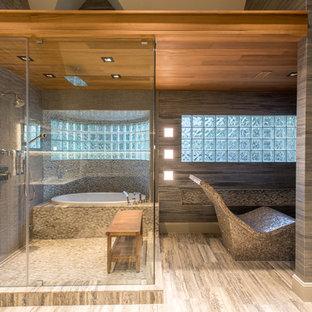 Modelo de sauna actual, grande, con armarios con paneles lisos, puertas de armario de madera oscura, bañera encastrada, baldosas y/o azulejos grises, baldosas y/o azulejos de porcelana, paredes grises, suelo de mármol, encimera de mármol y ducha con puerta con bisagras