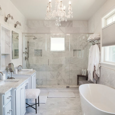 Bathroom - coastal master gray tile, white tile and marble tile marble floor and gray floor bathroom idea in New York with recessed-panel cabinets, white cabinets, gray walls, an undermount sink, marble countertops, a hinged shower door and gray countertops