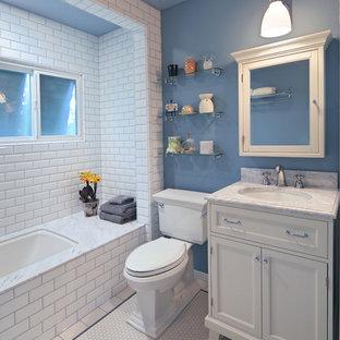 Immagine di una piccola stanza da bagno con doccia classica con lavabo sottopiano, ante bianche, top in marmo, vasca sottopiano, vasca/doccia, WC a due pezzi, piastrelle bianche, piastrelle in ceramica, pareti blu, pavimento con piastrelle in ceramica e ante in stile shaker