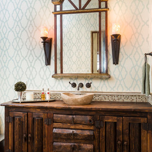 Inspiration for a mediterranean brown floor bathroom remodel in Austin with a vessel sink, wood countertops, furniture-like cabinets, dark wood cabinets and multicolored walls