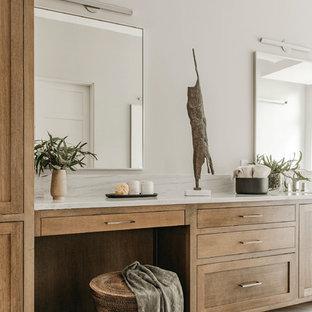 オースティンの大きいコンテンポラリースタイルのおしゃれなマスターバスルーム (シェーカースタイル扉のキャビネット、中間色木目調キャビネット、置き型浴槽、段差なし、ベージュの壁、磁器タイルの床、アンダーカウンター洗面器、珪岩の洗面台、マルチカラーの床、開き戸のシャワー、白い洗面カウンター) の写真