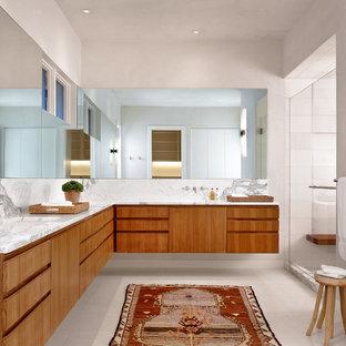 Ejemplo de cuarto de baño principal, actual, con armarios con paneles lisos, puertas de armario de madera oscura, ducha empotrada, baldosas y/o azulejos grises, baldosas y/o azulejos multicolor, baldosas y/o azulejos blancos, paredes grises y lavabo bajoencimera