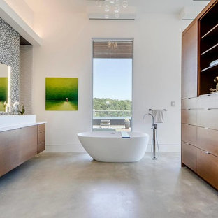 Trendy master multicolored tile and mosaic tile concrete floor freestanding bathtub photo in Austin with flat-panel cabinets, medium tone wood cabinets and white walls