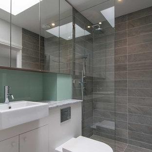 ロンドンの小さいコンテンポラリースタイルのおしゃれな浴室 (壁付け型シンク、フラットパネル扉のキャビネット、グレーのキャビネット、珪岩の洗面台、ドロップイン型浴槽、オープン型シャワー、一体型トイレ、グレーのタイル、セラミックタイル、グレーの壁、セラミックタイルの床) の写真