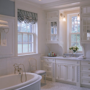 Elegant alcove bathtub photo in Boston with recessed-panel cabinets and an undermount sink