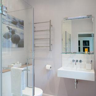 Diseño de cuarto de baño con ducha, actual, pequeño, con ducha a ras de suelo, sanitario de una pieza, baldosas y/o azulejos blancos, baldosas y/o azulejos de cerámica, paredes púrpuras, lavabo suspendido, encimera de madera, suelo marrón y ducha con puerta con bisagras