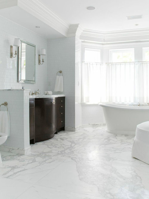 Example of a large classic master white tile marble floor and white floor  freestanding bathtub design