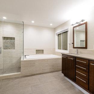 На фото: большая главная ванная комната в современном стиле с плоскими фасадами, темными деревянными фасадами, угловой ванной, угловым душем, бежевой плиткой, керамогранитной плиткой, бежевыми стенами, полом из винила, врезной раковиной, столешницей из плитки, бежевым полом и душем с распашными дверями с