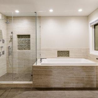 Diseño de cuarto de baño principal, actual, grande, con armarios con paneles lisos, puertas de armario de madera en tonos medios, bañera esquinera, ducha esquinera, baldosas y/o azulejos beige, baldosas y/o azulejos de porcelana, paredes beige, suelo vinílico, lavabo bajoencimera, encimera de azulejos, suelo beige y ducha con puerta con bisagras