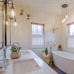Foto de cuarto de baño de estilo de casa de campo con armarios con paneles lisos, bañera exenta, baldosas y/o azulejos blancos, baldosas y/o azulejos de cemento, paredes amarillas, lavabo bajoencimera, encimera de cuarzo compacto y suelo gris