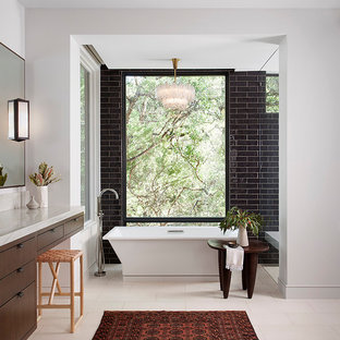 Ejemplo de cuarto de baño contemporáneo con armarios con paneles lisos, puertas de armario de madera en tonos medios, bañera exenta, baldosas y/o azulejos negros, baldosas y/o azulejos de cemento, paredes blancas, suelo beige y encimeras blancas