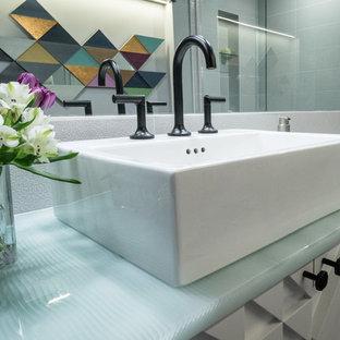 Cette image montre une petite salle de bain design avec des portes de placard blanches, un WC séparé, un carrelage blanc, des carreaux de porcelaine, un mur blanc, un sol en carrelage de porcelaine, une vasque, un plan de toilette en verre, un sol gris et un plan de toilette vert.