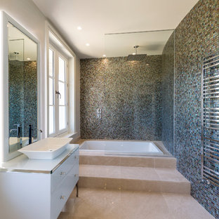 This is an example of a medium sized traditional bathroom in Surrey with flat-panel cabinets, white cabinets, a japanese bath, a shower/bath combination, blue tiles, mosaic tiles, blue walls, a vessel sink, beige floors, an open shower and white worktops.