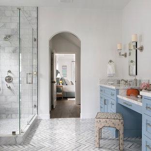 Diseño de cuarto de baño principal, clásico renovado, grande, con puertas de armario azules, bañera exenta, ducha esquinera, sanitario de una pieza, baldosas y/o azulejos de mármol, paredes blancas, suelo de mármol, lavabo bajoencimera, encimera de mármol, ducha con puerta con bisagras, armarios con paneles empotrados, baldosas y/o azulejos blancos, suelo gris y encimeras blancas