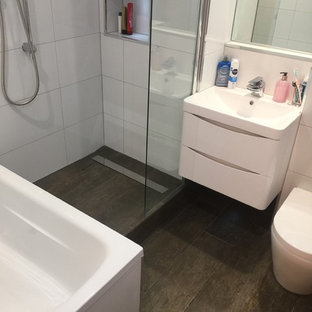 Inspiration for a small contemporary bathroom in London with flat-panel cabinets, white cabinets, a built-in bath, a two-piece toilet, brown tiles, ceramic tiles, white walls, ceramic flooring, a wall-mounted sink and tiled worktops.