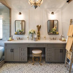 Réalisation d'une grand salle de bain principale tradition avec un placard à porte persienne, des portes de placard en bois sombre, une baignoire indépendante, un espace douche bain, un carrelage gris, des carreaux de porcelaine, un mur beige, un sol en carrelage de porcelaine, un lavabo encastré, un plan de toilette en surface solide, un sol multicolore et une cabine de douche à porte battante.